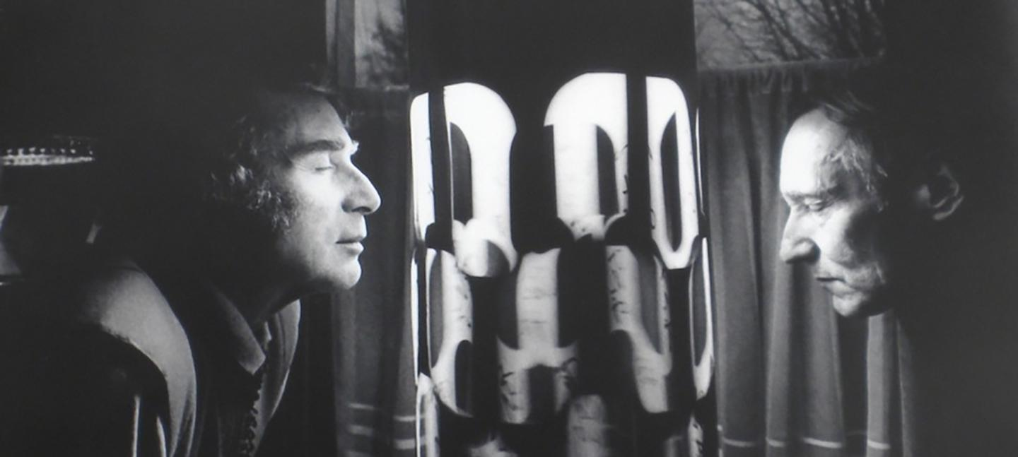 A black and white photo of two men looking at a light installation / dream machine