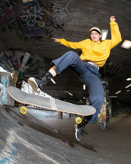 A female skateboarder mid-air performing a trick on a skate ramp