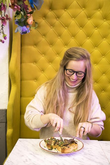 A woman sat in a yellow high-backed velvet armchair eats mushrooms and truffles on toast