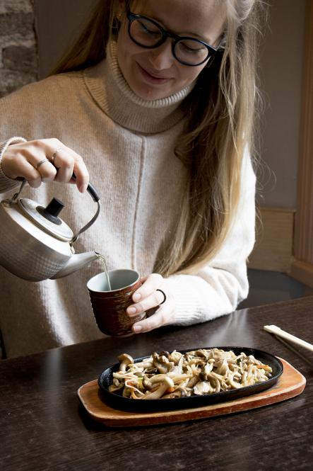 A woman pours a cup of green tea in from of a plate of stir-fried mushrooms at Eat Tokyo