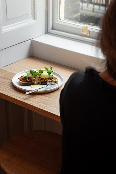 A woman sits with a plate of food in Watch House cafe at Somerset House
