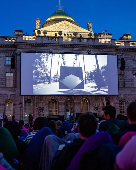 People watching a film on an outdoor cinema screen at Film4 Summer Screen at Somerset House
