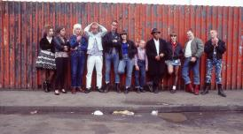 Film still of a group of people standing against a wall