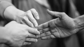 A black and white photo of three different hands, the tips of their fingers touching at the center of the image