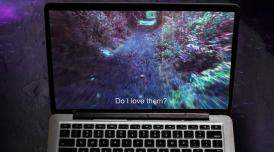 A photo of a macbook floating through what looks like a galaxy. On the open screen are the words 'Do I love them?'
