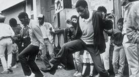A group of men dancing in the street at Notting Hill Carnival