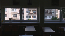 A still from Gerda Paliušytė's film Early Winter. It depicts a class room, with empty chairs and desks, with windows, looking out to buildings across the way.