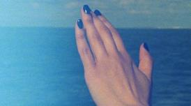 A still from Ana Vaz's film Occidente. It shows a woman's manicured hands with a shiny dark blue acrylic on a background of sea and sky,