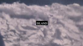 A still from Laura Grace Ford & Sam William's film ISLAND. It shows a fuzzy cloud-like substance with word ISLAND printed on it