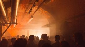Crowd of people at a lice music event with lasers and smoke in The Deadhouse at Somerset House