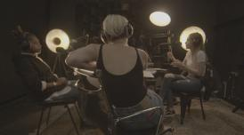 A photo of Jessie recording with two other speakers in a room with spotlights and recording equipment.