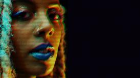 A photo of Juliana Huxtable, with a glitch effect and a black background.