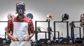 A photo of a man stood in front of 3-D printing equipment wearing a red shirt and a plastic face shield.