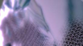 A blurred close-up of some knitted fabric in a blue, grey palette
