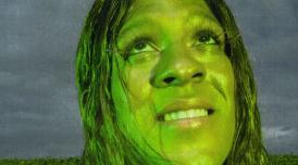 A person photographed in green lighting looking upwards