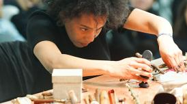 A photo of Elaine Mitchener working at a table, constructing an uknown object, In the background you can see  people sat watching.