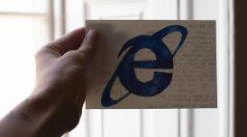 A photo of a hand holding a postcard. On the front of the postcard is the letter e in blue.