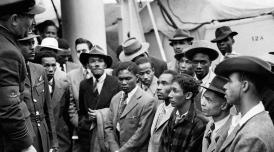 Jamaican immigrants being addressed shortly after their arrival in Tilbury by RAF officials from the Colonial Office in 1948. Photograph: PA