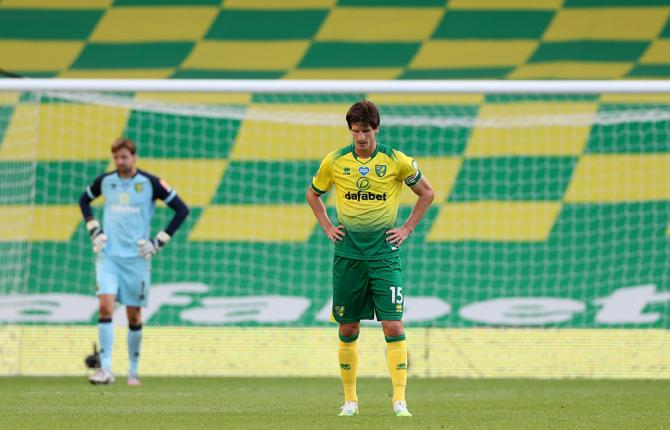 Two footballers stand in front of a goal in an empty stadium