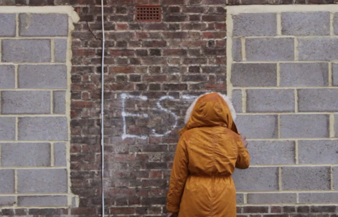 A still from 'Estate: a Reverie', 2015 by Andrea Luka Zimmerman. It shows someone in a orange coat with their hood up spraypainting a brick wall