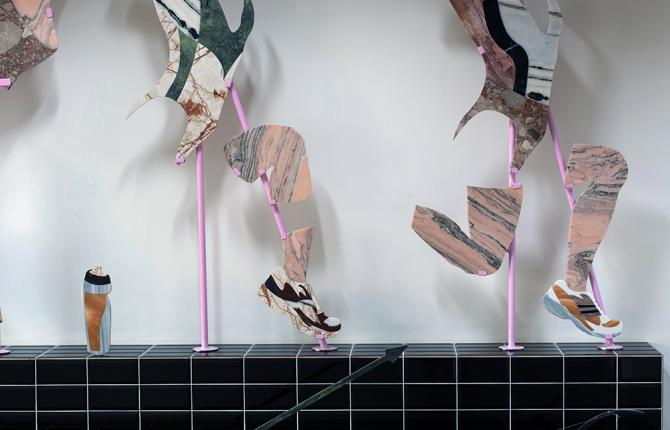 Sculpture of running legs and trainers on a black tiled platform in an art gallery