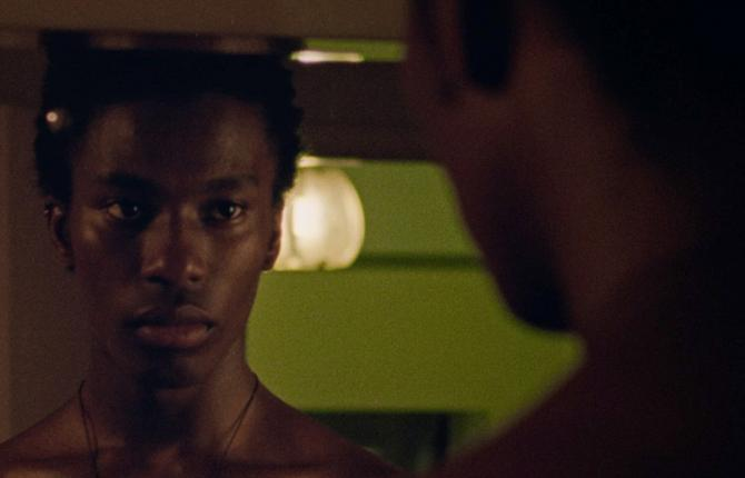 A still from a film by Iggy London. It shows a Black man, loking into a mirror, where we can see a reflection of his face.