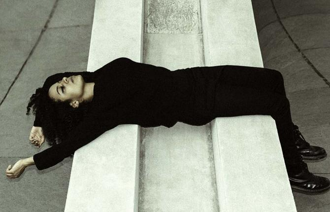 Jessica Ekomane in a black suit laying on her back on a white stone structure