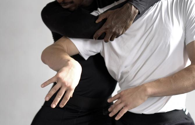 A black man and a white man in motion, dancing