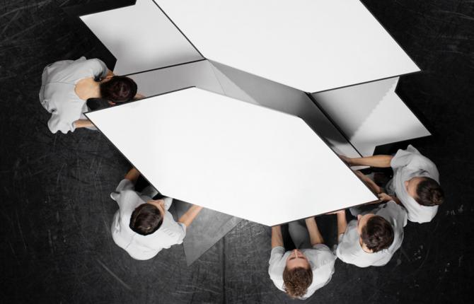An artwork by Jasmina Cibic. An aerial view of 5 people moving a geometric, white shape across a black floor.